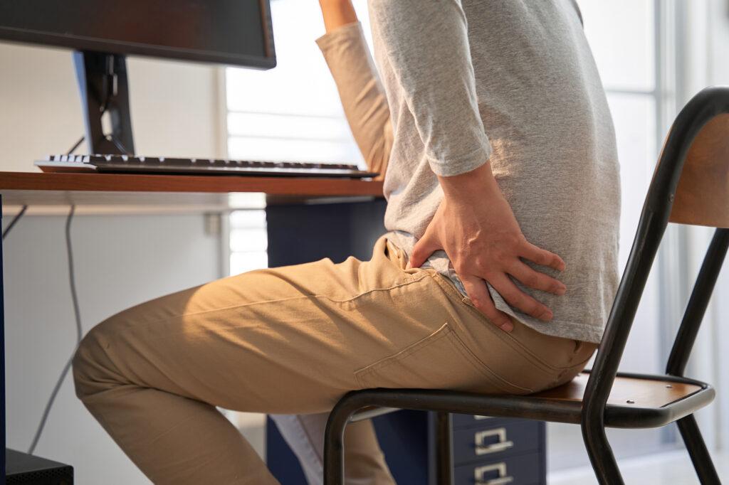 man sitting at desk holding hip